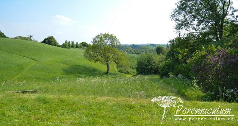 Výhled přes květnatou louku, která patří majitelům zahrady, do daleké údolní krajiny.