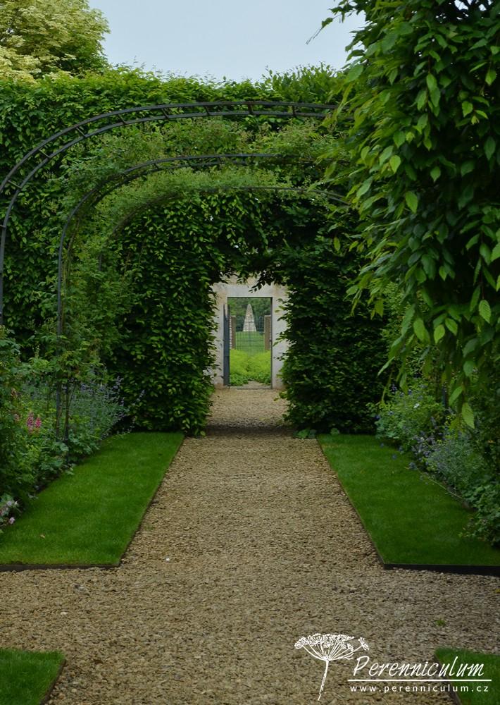 Z Růžové zahrady lze skrz dveře ve zdi walled garden vidět vzdálený kamenný obelisk.