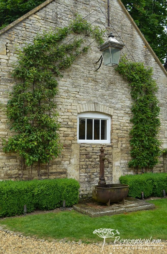 Protor po pravé straně domu a zároveň zadní vchod do domu slouží jako parkoviště. U stěny bývalých stájí našla místo stará pumpa.