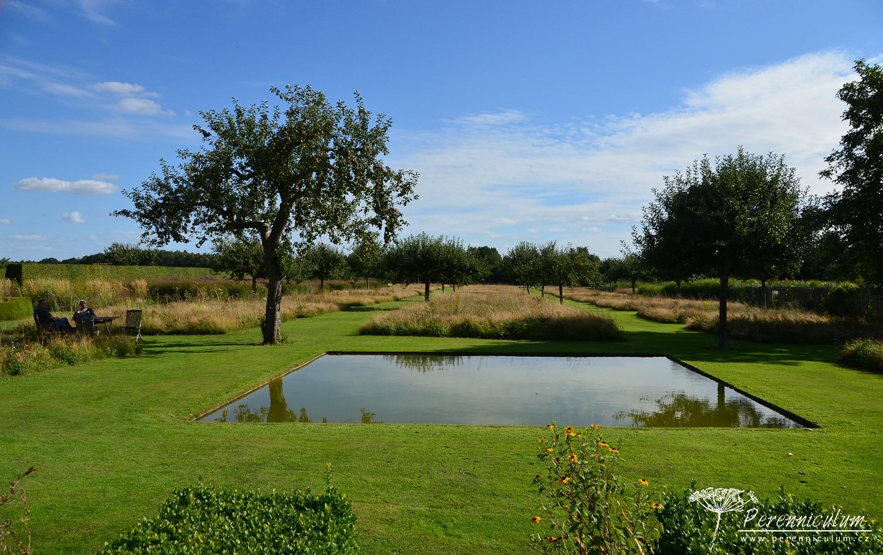 Starému sadu majitelé vtiskli určitou formálnost nízce sečenými pruhy trávníku a čtverci lučních společenstev. Čtvercová vodní plocha jen podtrhuje tento jednoduchý koncept.